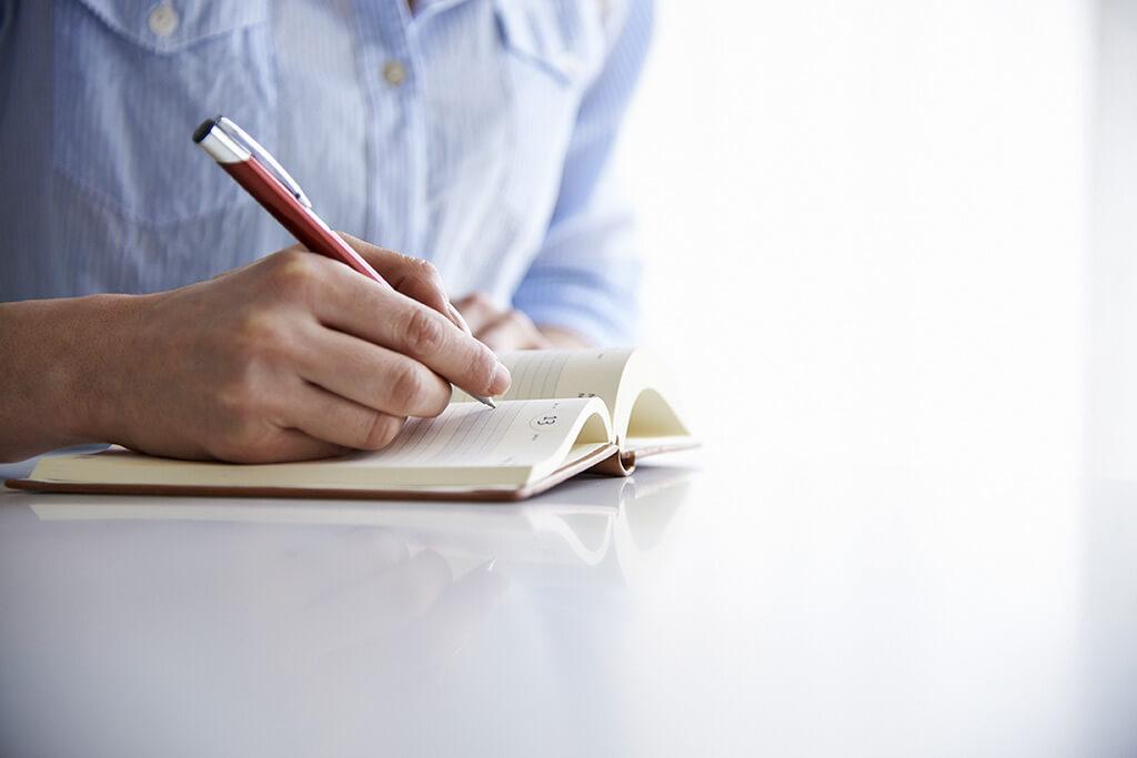 Eine Person notiert sich etwas in einem Terminkalender.