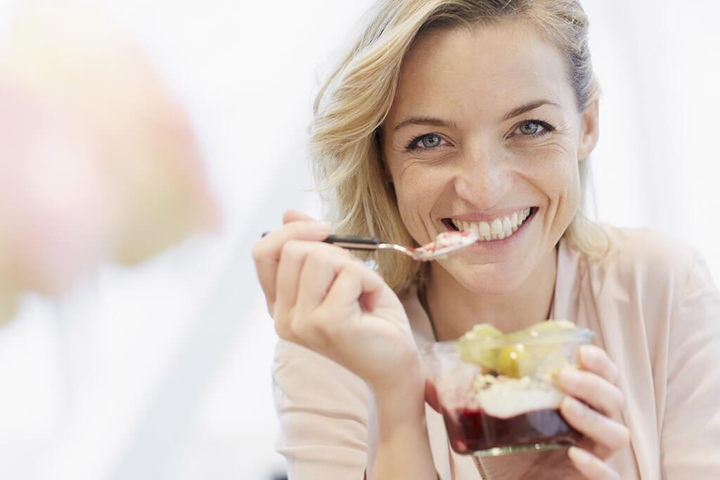 Eine Frau lächelt in die Kamera und isst einen Nachtisch.