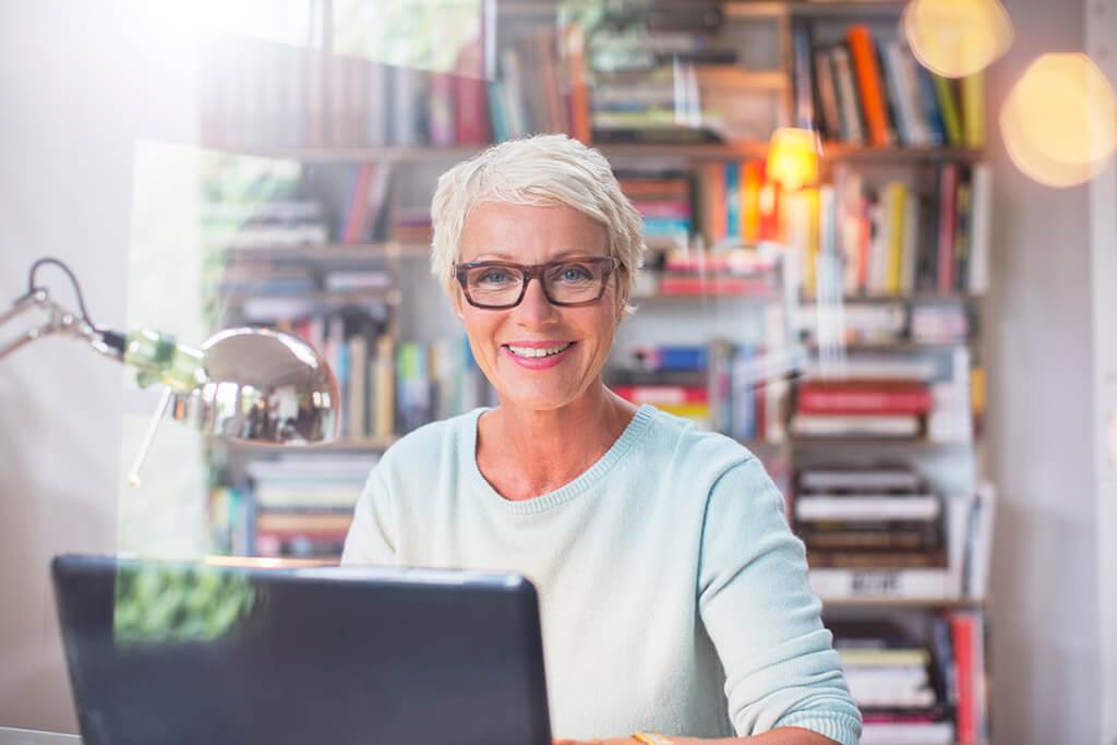 Eine ältere Frau sitzt vor ihrem Laptop und lächelt.