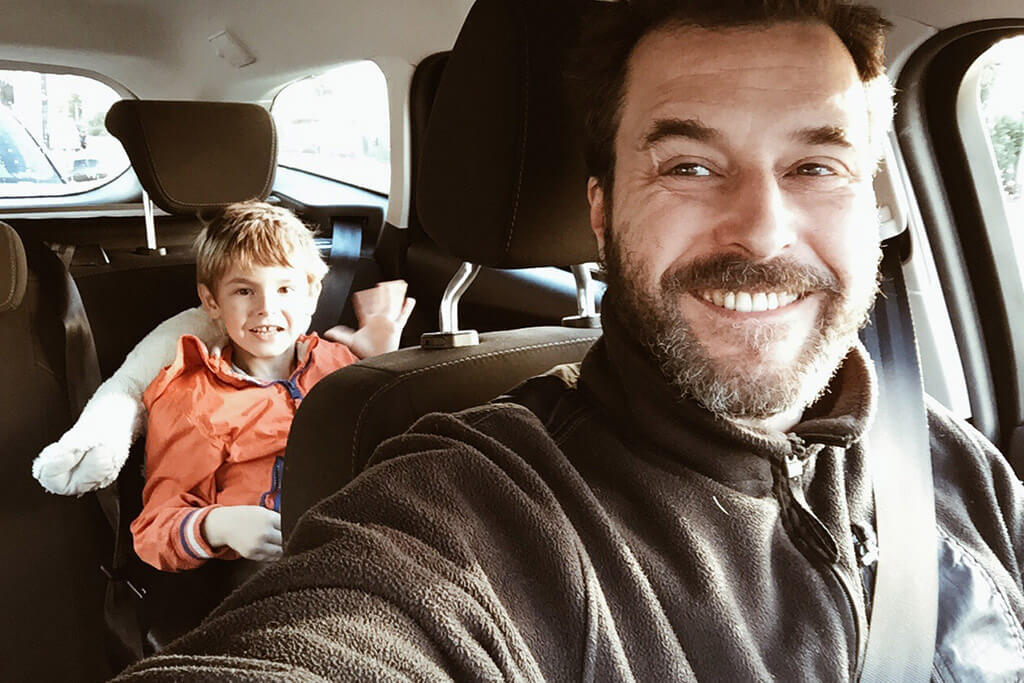 Ein Vater sitzt mit seinem Sohn im Auto.