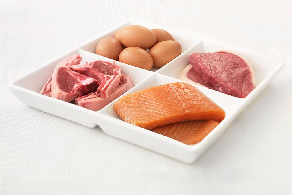 Ein Teller viergeteilt, mit Eiern, Steak, Lachs, und Lammfleisch drauf.