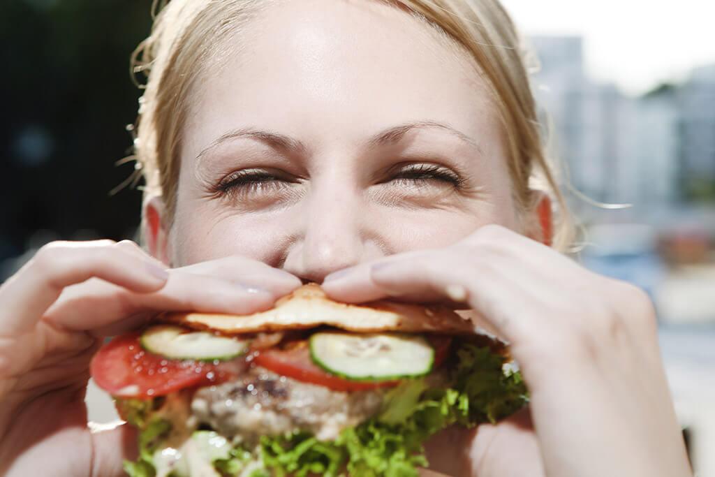 Eine Frau beißt in einen Hamburger rein.
