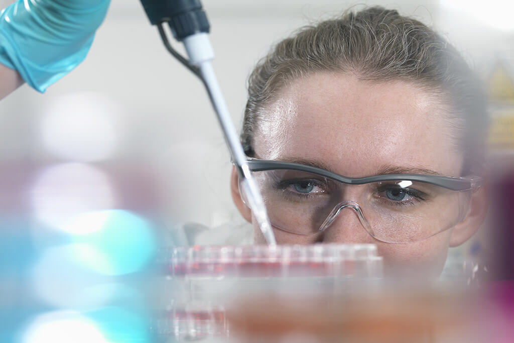 Eine Frau mit Schutzbrille arbeitet im Labor.