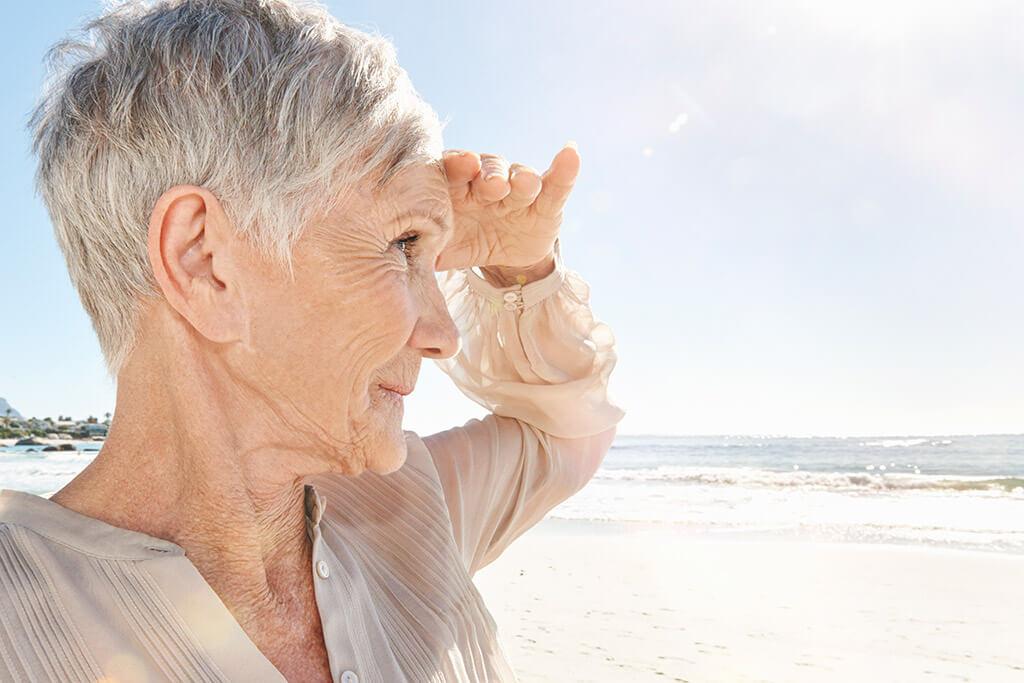 Eine ältere Frau steht am Strand und schaut auf das Meer.