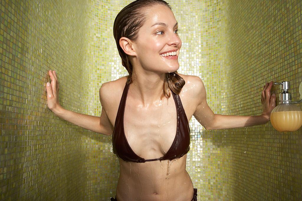Eine Frau im Bikini steht in einer Dusche und schaut heraus.