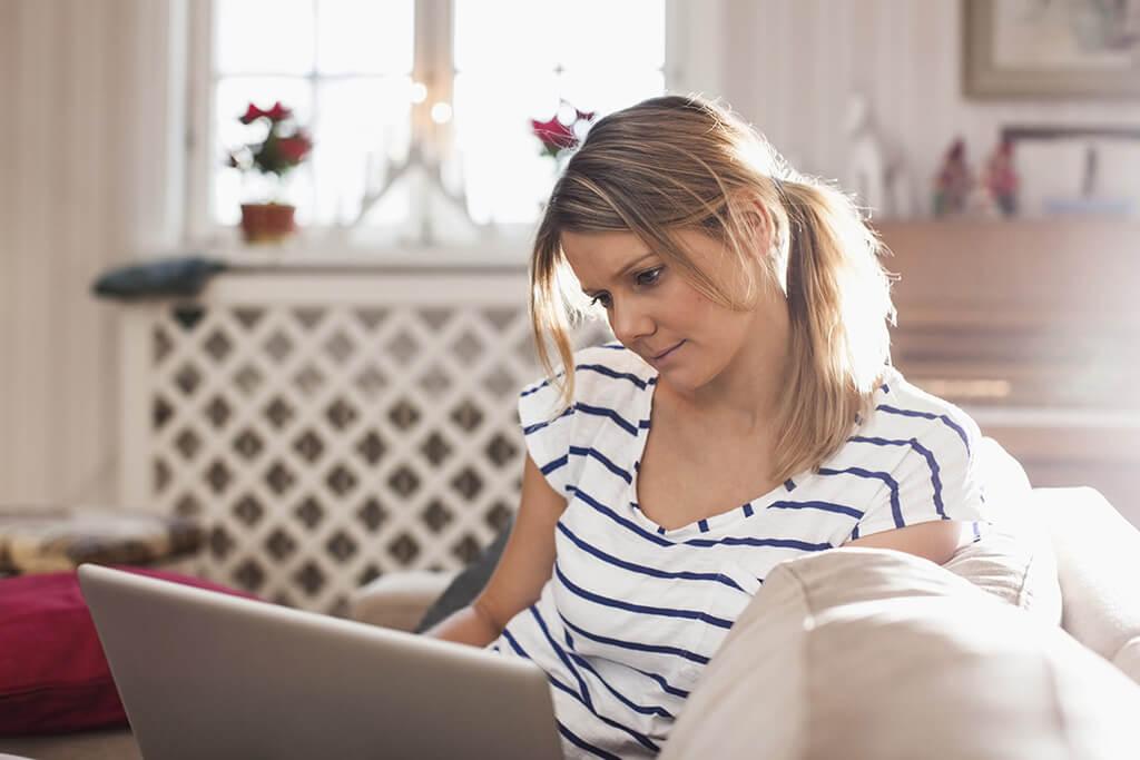 Eine Frau sitzt auf dem Sofa und liest etwas auf ihrem Laptop.