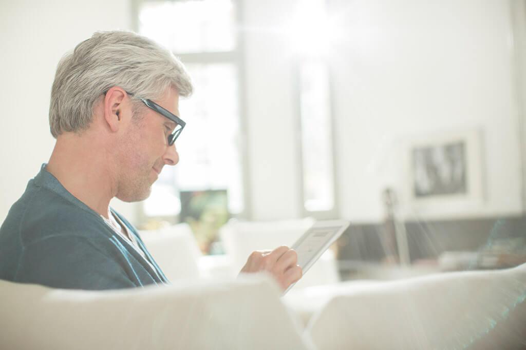 Ein Mann sitzt auf dem Sofa und liest etwas auf seinem Tablet.