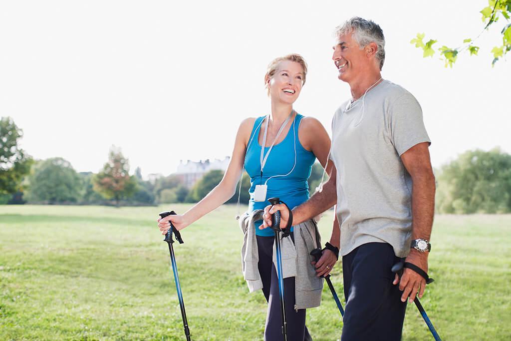 Ein älteres Paar beim Nordic Walking.