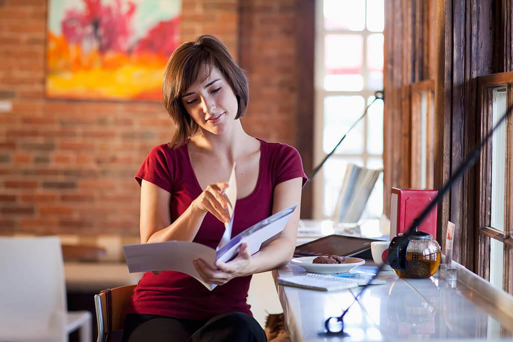 Eine junge Frau sitzt an einer Bar trinkt Tee und liest in einem Heft.
