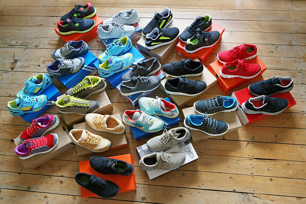 Mehrere bunte Turnschuhe stehen auf Schuhkartons.
