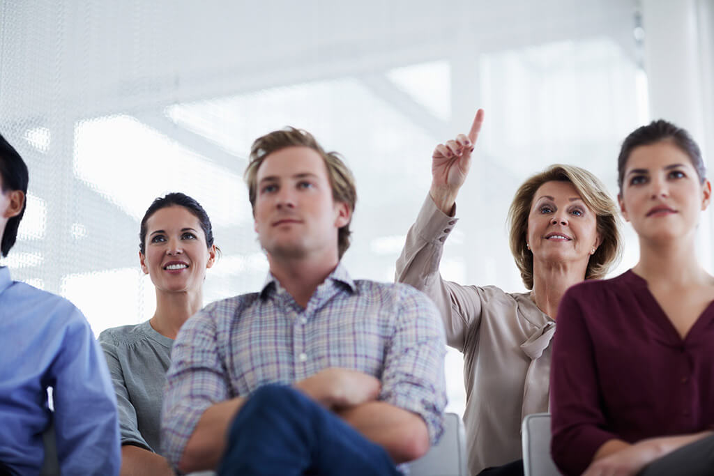 Eine Gruppe Personen hören einem Vortrag zu und eine Frau meldet sich.