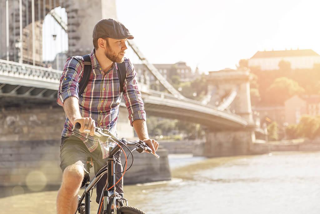Ein junger Mann fährt mit seinem Fahrrad an einer Brücke