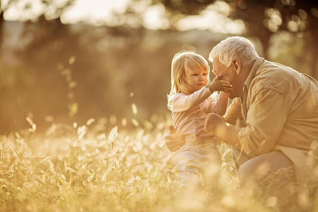 Ein Großvater mit seiner Enkelin in einem Feld.