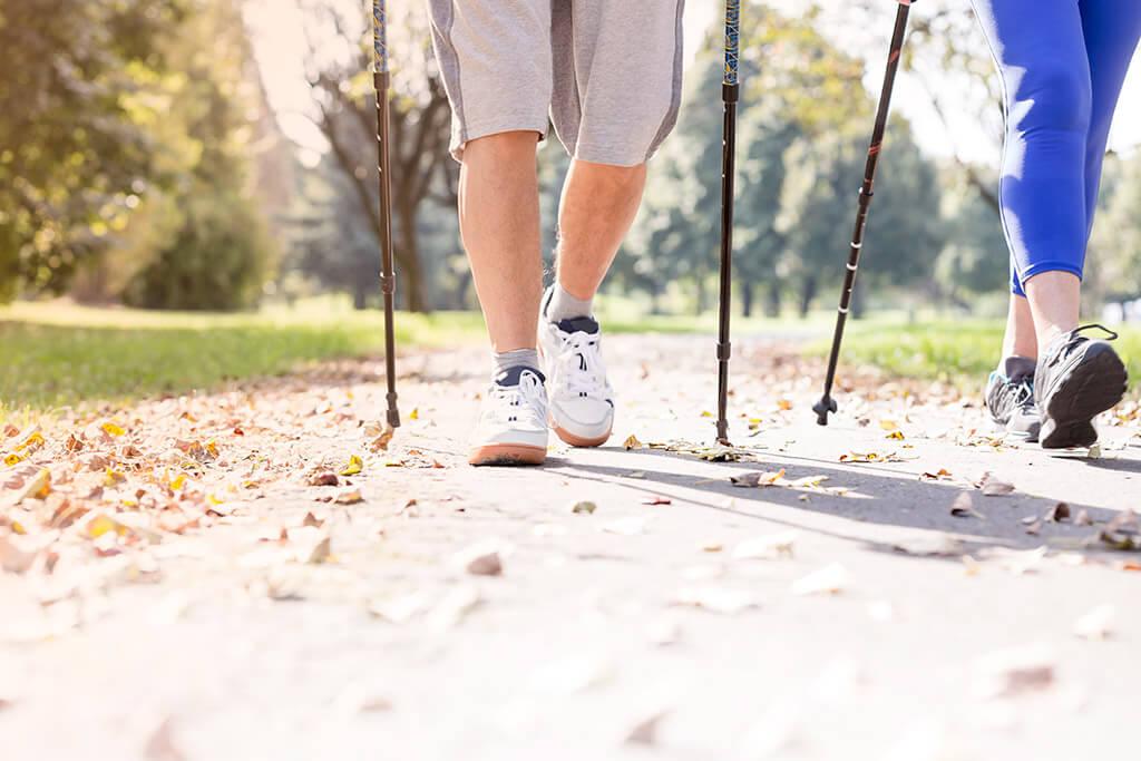 Die Beine von zwei Personen beim Nordic Walking.