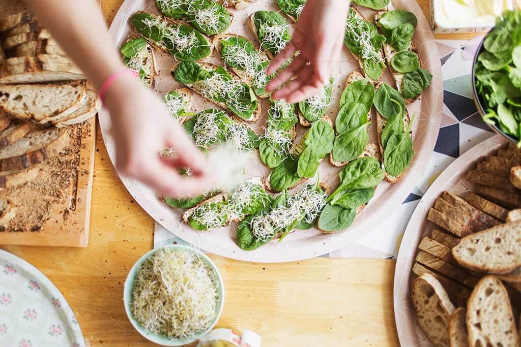 Zwei Hände streuen Käse auf kleine Brote.