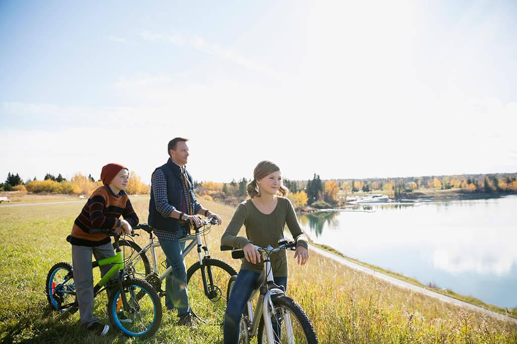 Zwei Kinder und ihr Vater machen eine Pause von ihrere fahrradtour und schauen sich einen See an.