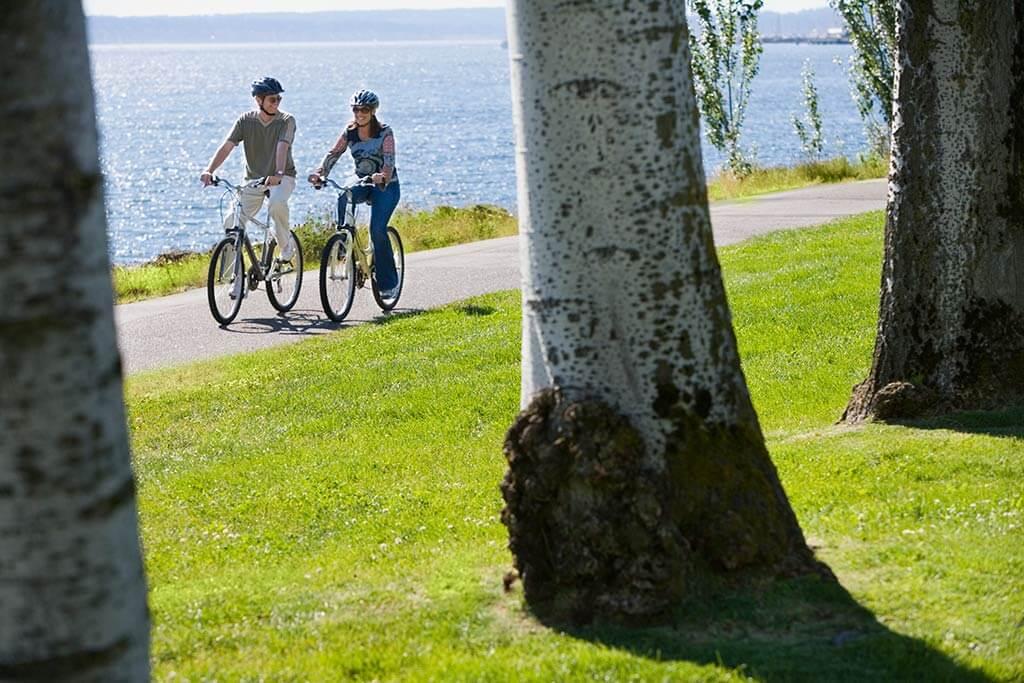 Ein Paar fährt Fahrrad am See.