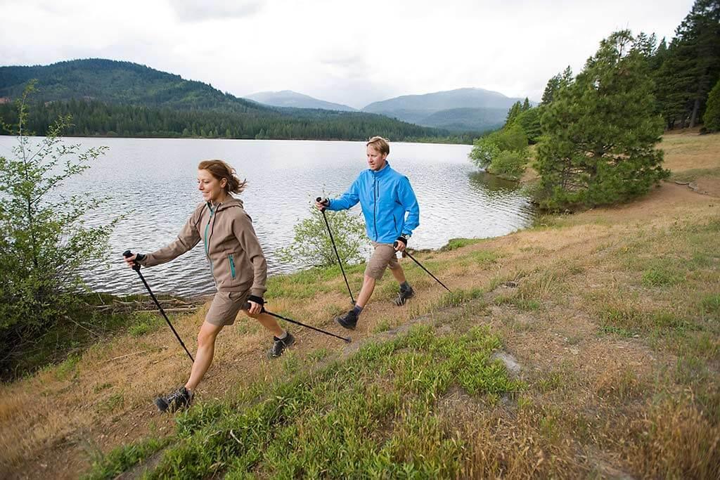 Ein Paar macht Nordic Walking an einem See.