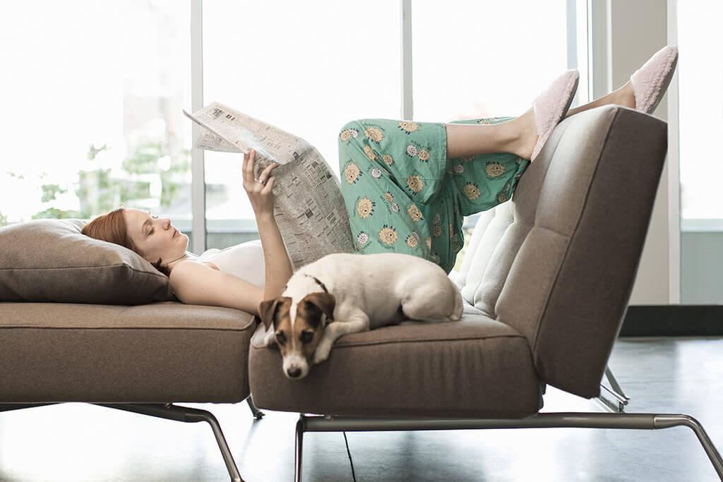 Eine Frau liegt mit ihrem hund auf einem Sofa und liest Zeitung.