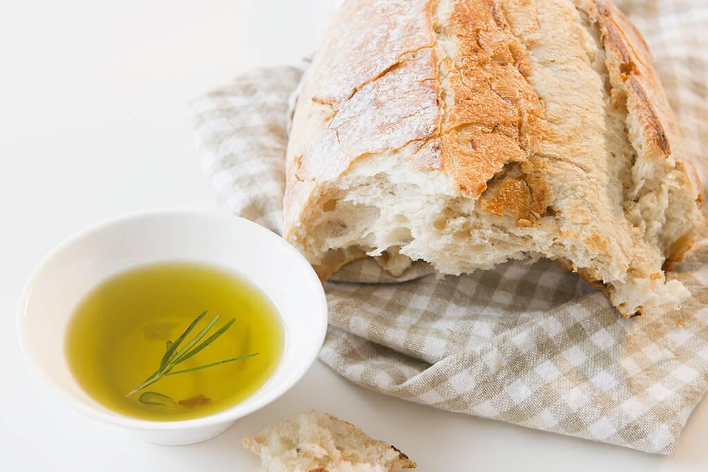 Ein frisches Brot mit einer kleinen Schüssel Olivenöl.
