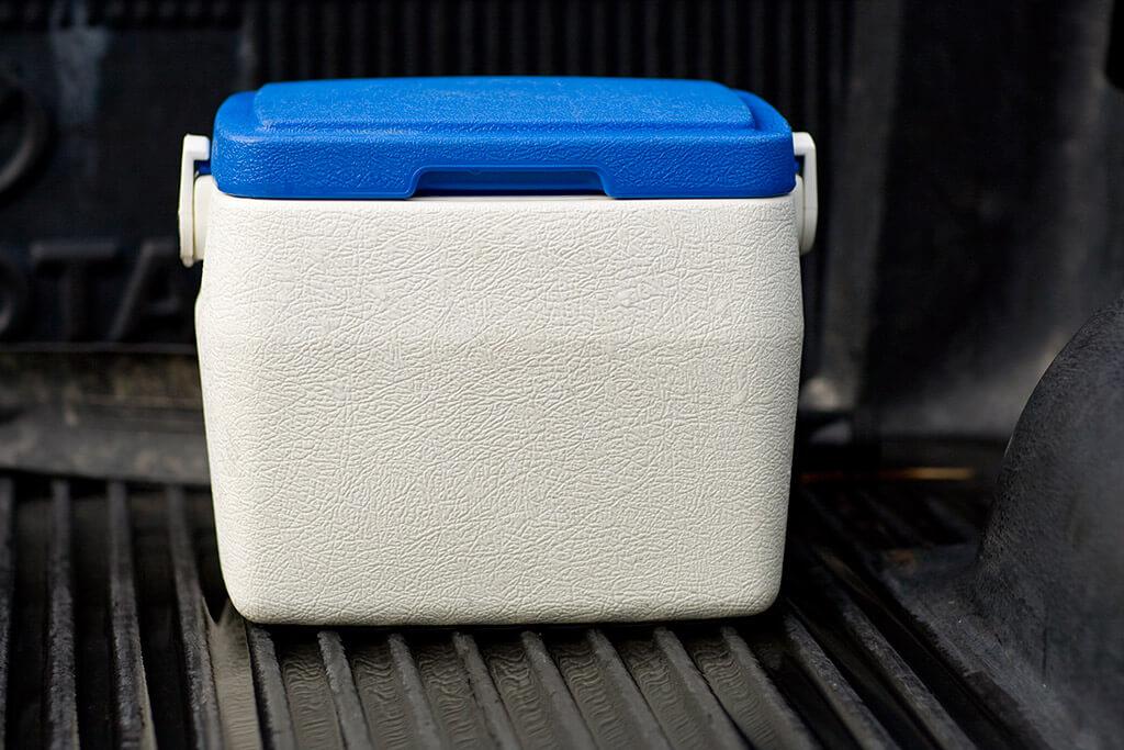 Eine weiße Kühlbox mit blauem Deckel.