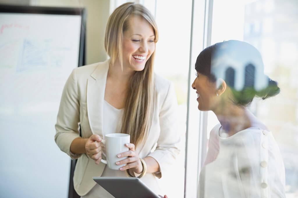 Zwei Frau stehen an einem Fenster und unterhalten sich und trinken dabei einen Kaffee.