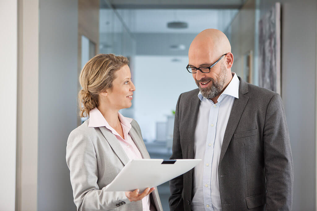 Eine Frau und ein Mann im Anzug unterhalten sich miteinander.