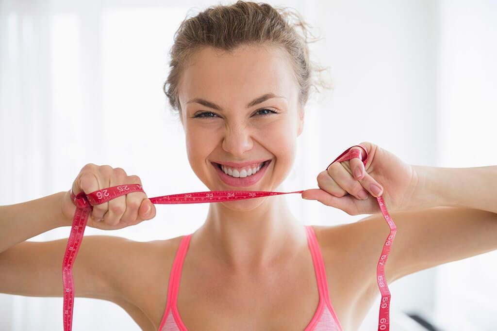 Eine Frau zieht ein Meterband mit ihren Händen auseinander.