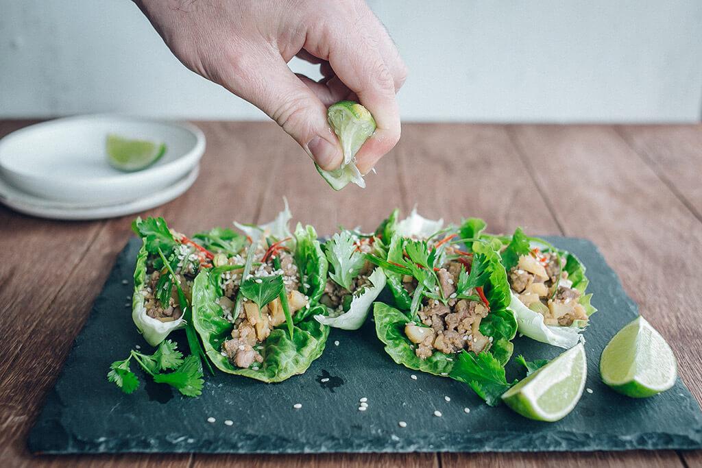 Eine Hand presst Limettensaft auf Tacos in einem Salatblatt.