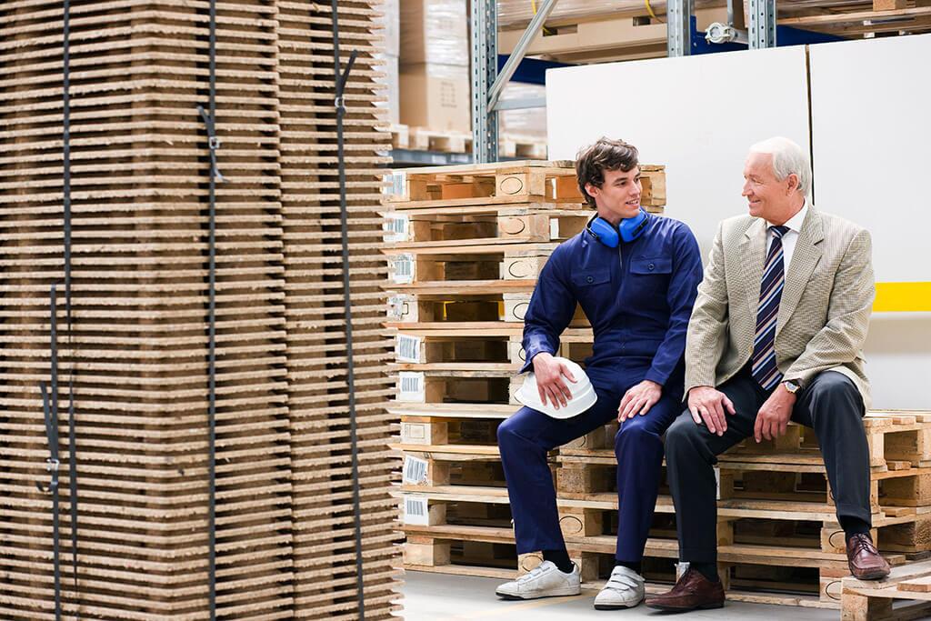 Ein Mann in Arbeitskleidung und ein Mann im Anzug sitzen auf Paletten.