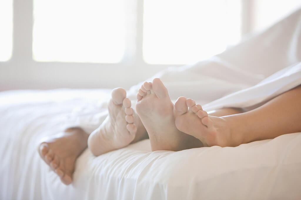 Vier Füße die unter einer Bettdecke hervorschauen.