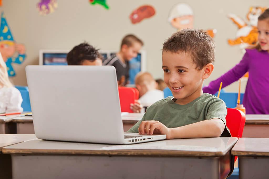 Ein kleiner Junge sitzt lachend vor einem Laptop in der Schule.