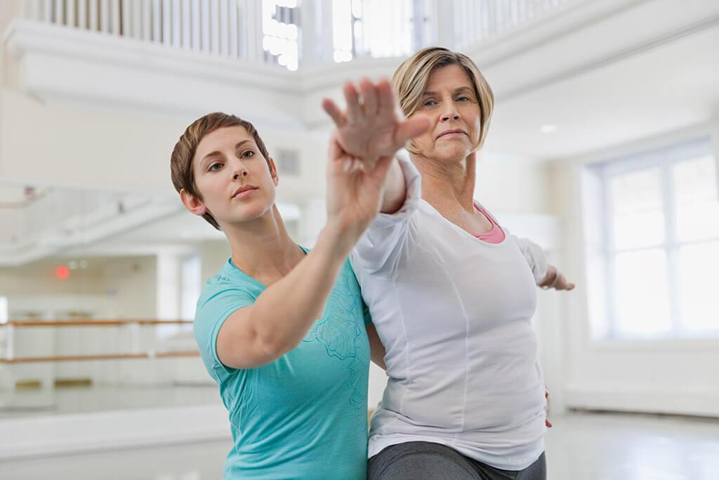 Zwei Frauen machen zusammen Gymnastikübungen.