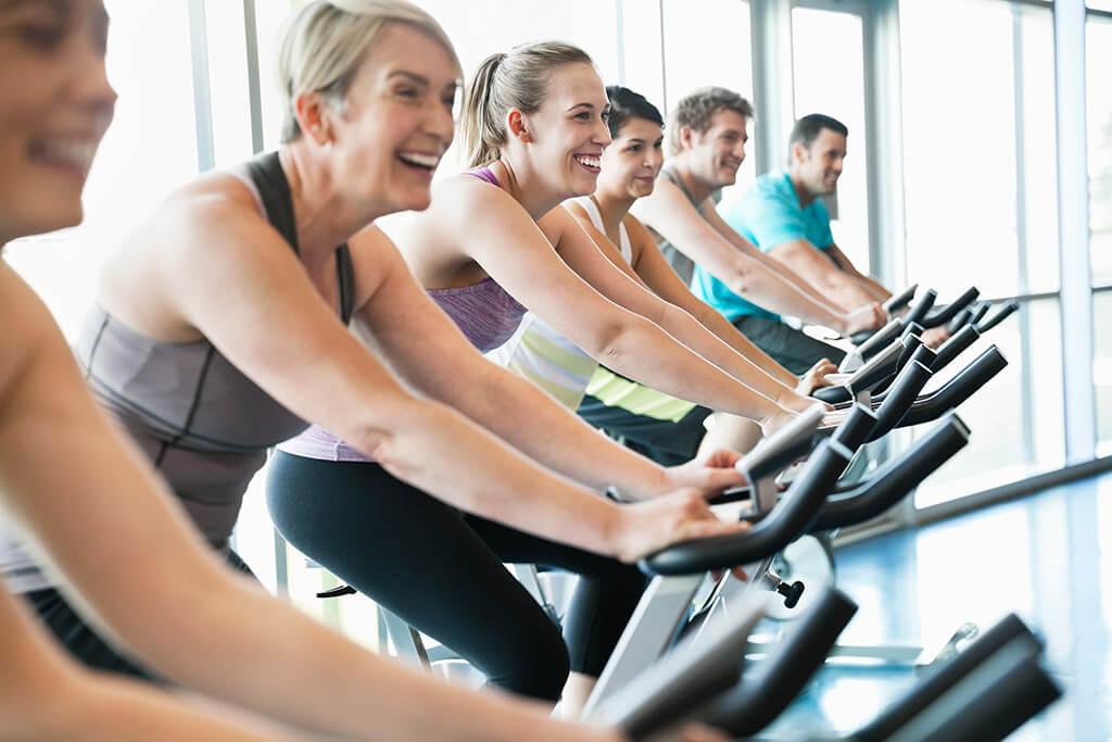 Eine Gruppe im Fitnessstudio auf Fahrrädern.