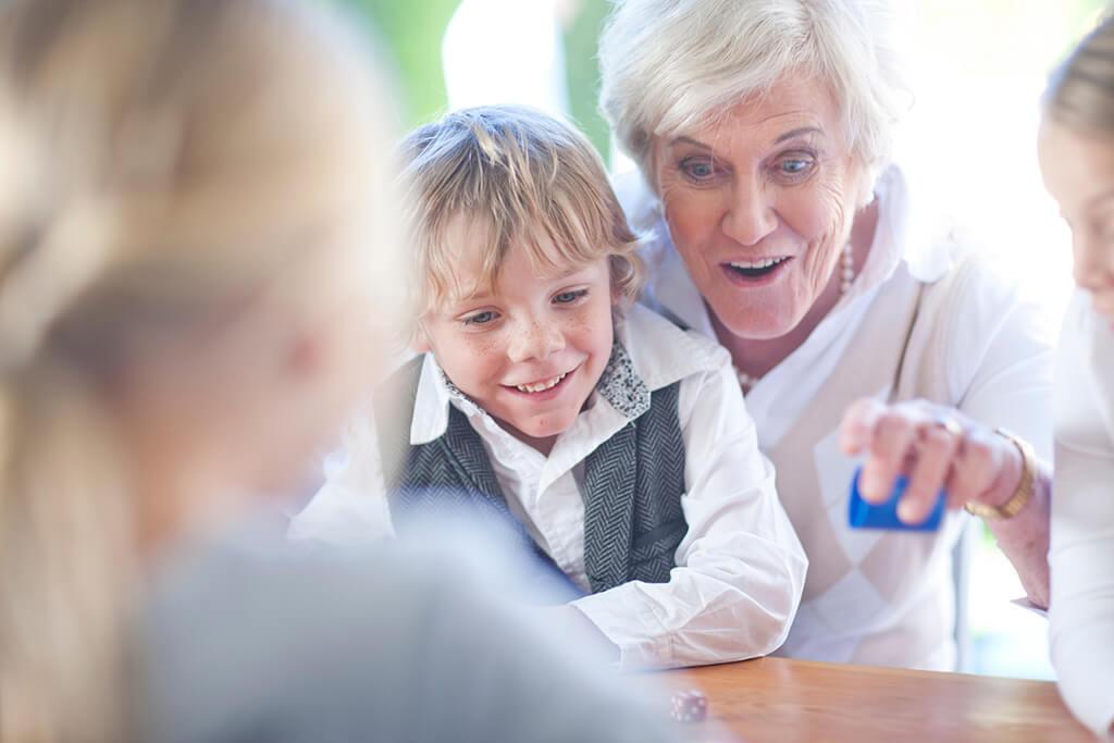 Eine Großmutter spielt mit ihrem Enkel und der Familie ein Spiel.