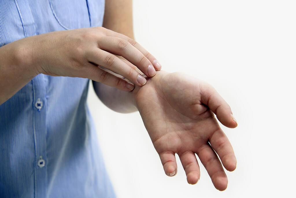 Eine Person kratzt ihren Arm.