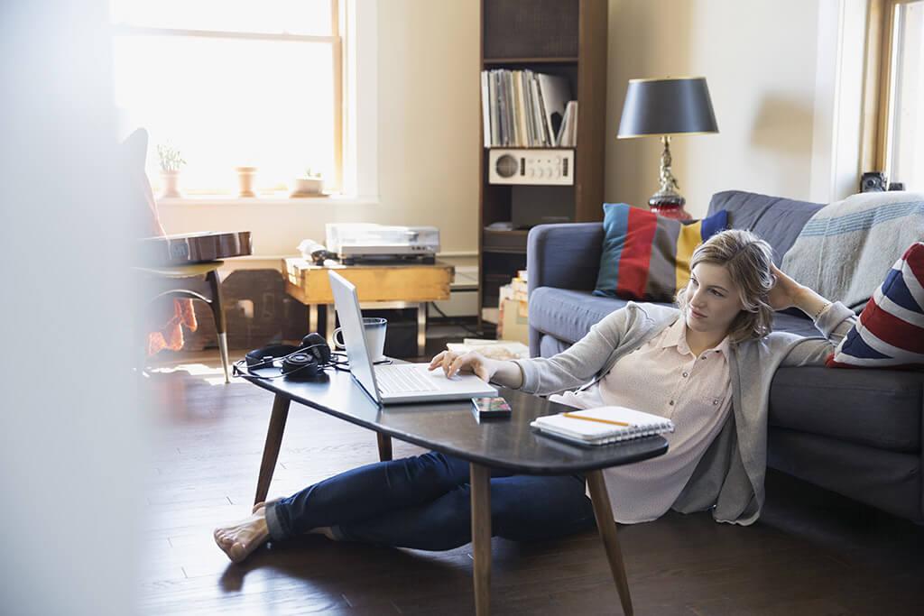 Eine Frau sitzt auf dem Boden vor ihrem Sofa und arbeitet an ihrem Laptop.