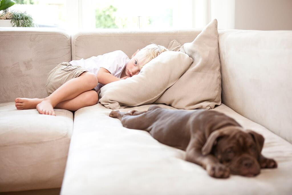 Ein kleiner Junge liegt traurig mit einem Hund auf einem Sofa.