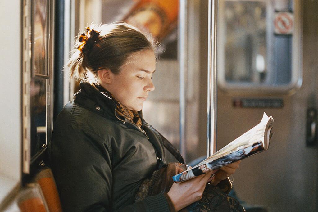 Eine Frau liest eine Zeitschrift in der Bahn.