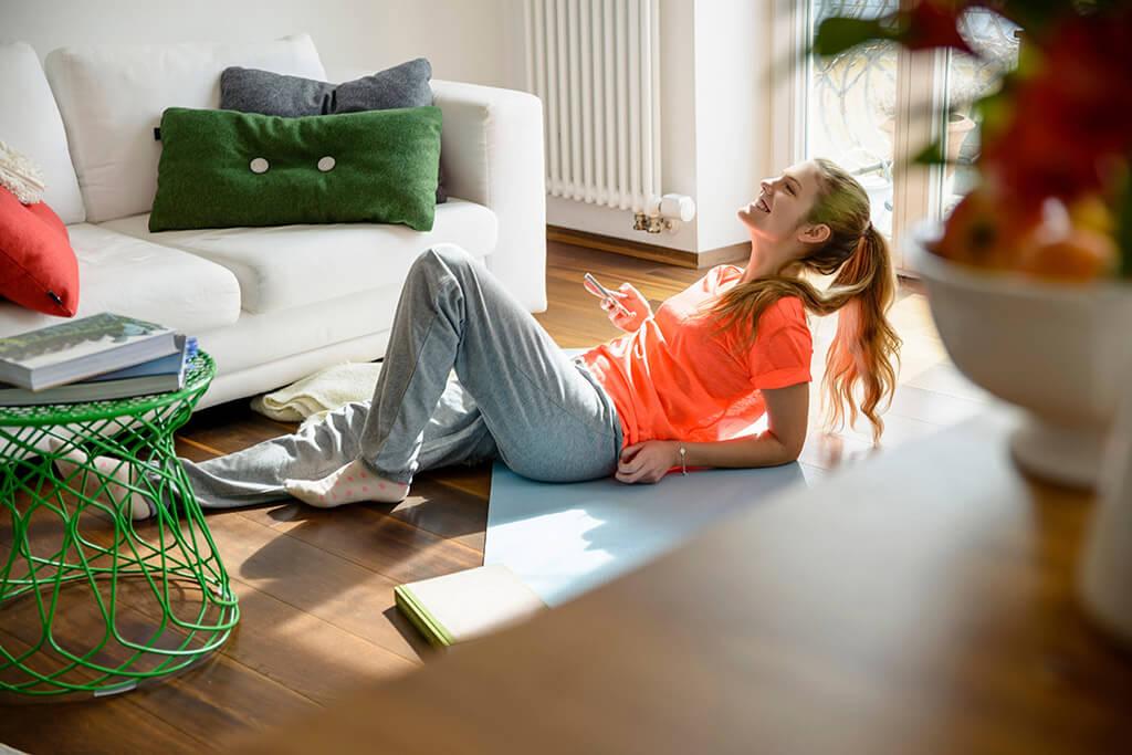 Eine Frau macht Sport auf dem Boden im Wohnzimmer.