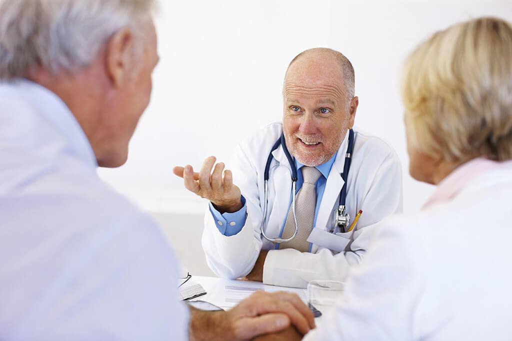 Ein Arzt spricht mit einem älteren Ehepaar.
