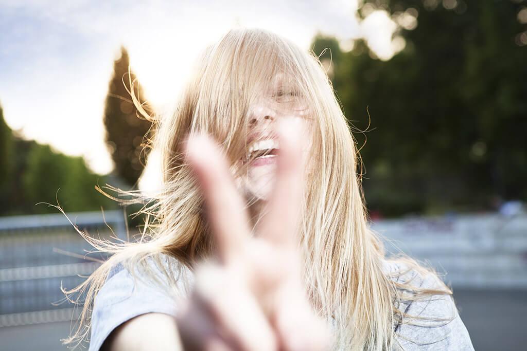 Einer lachenden Frau wehen die Haare ins Geischt.