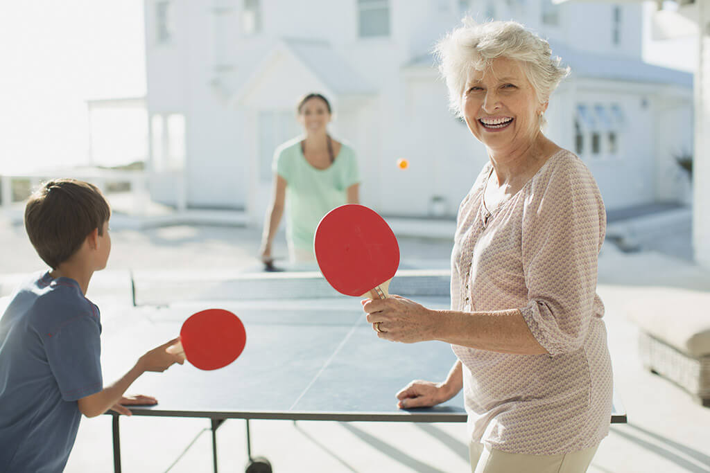Eine Großmutter spielt Tischtennis mit ihrem Enkel und seiner Mutter.