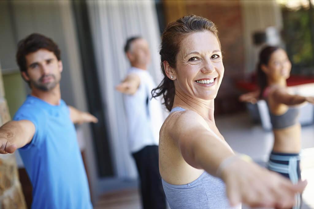 Mehrere Personen machen zusammen Yoga.
