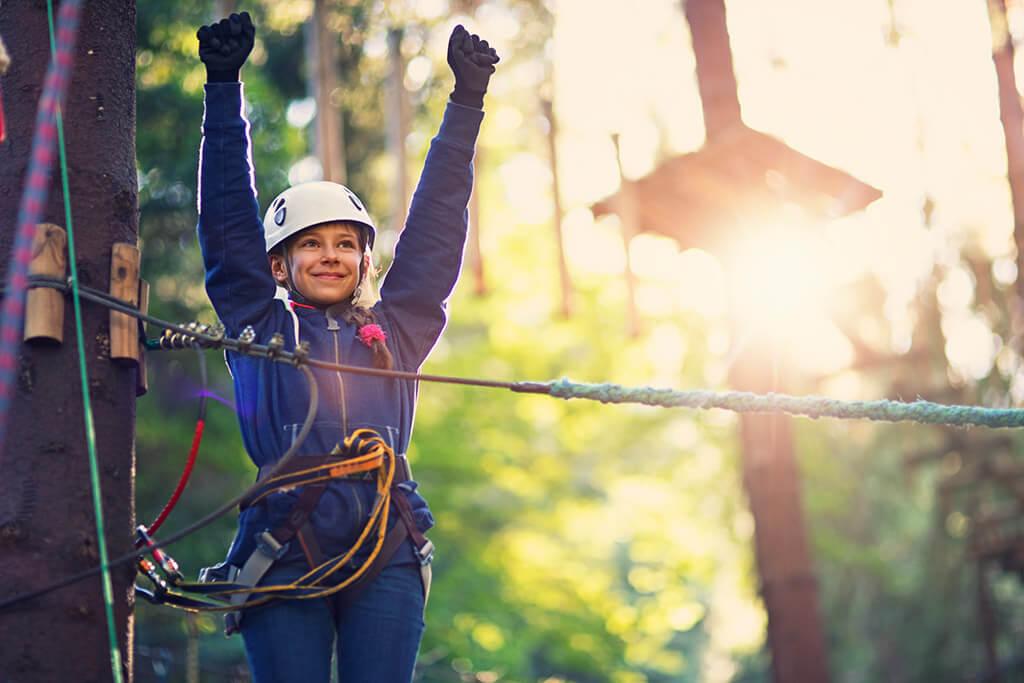 Ein Mädchen klettert einen Parcours im Wald.