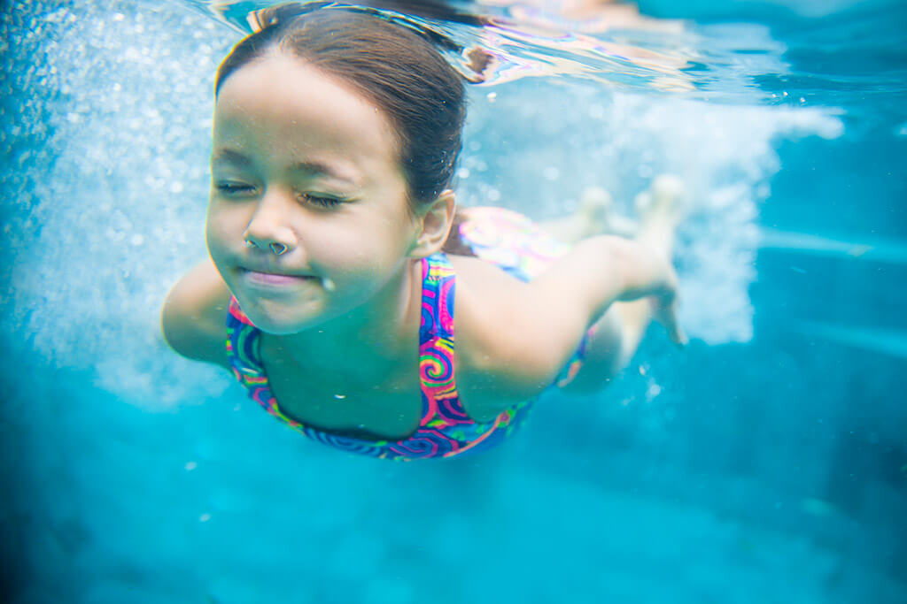 Ein Mädchen taucht in einem Pool.