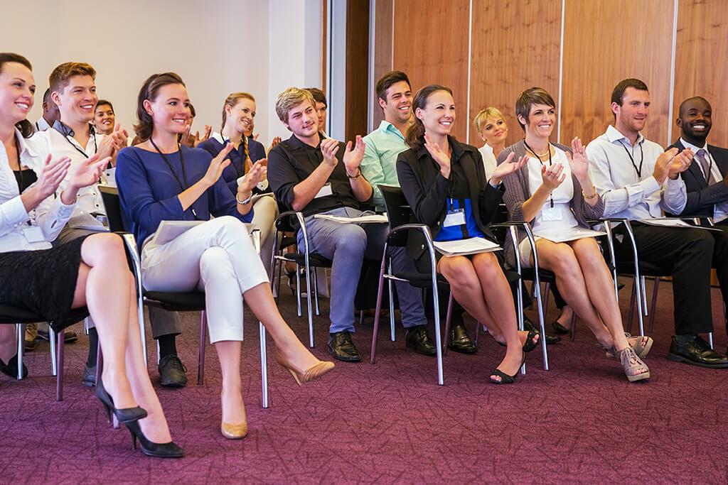 Mehrere Personen sitzen bei einem Vortrag und applaudieren.