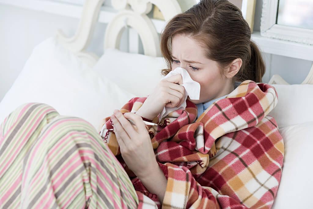 Eine Frau mit Erkältung sitzt auf dem Sofa und putzt sich die Nase.