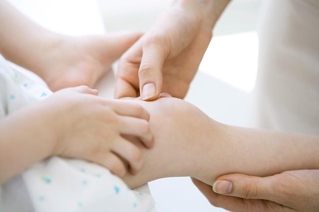 Arzt untersucht Knie eines Kindes.