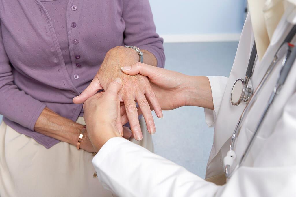 Eine Ärztin untersucht die Hand einer älteren Frau.